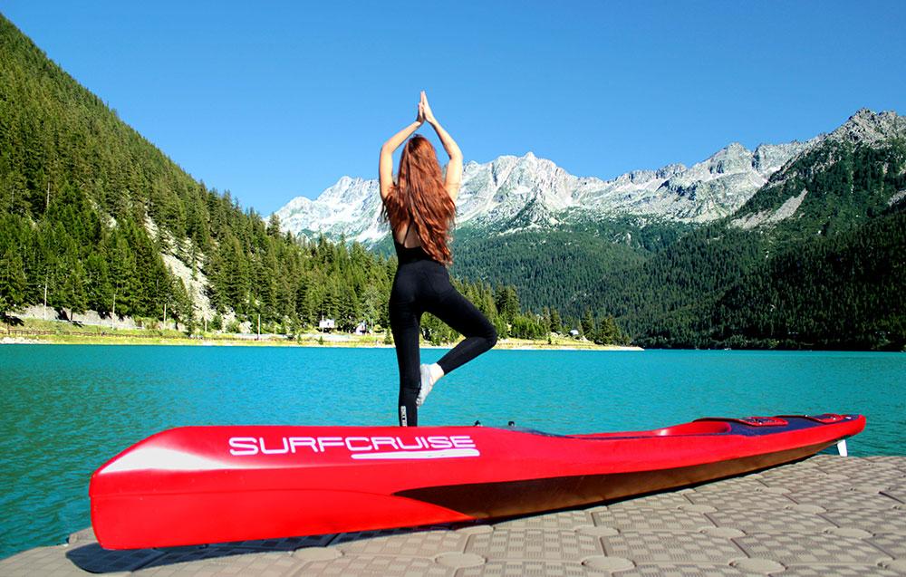 Donna con canoa kayak surfcruise su lago alpino, relax e yoga