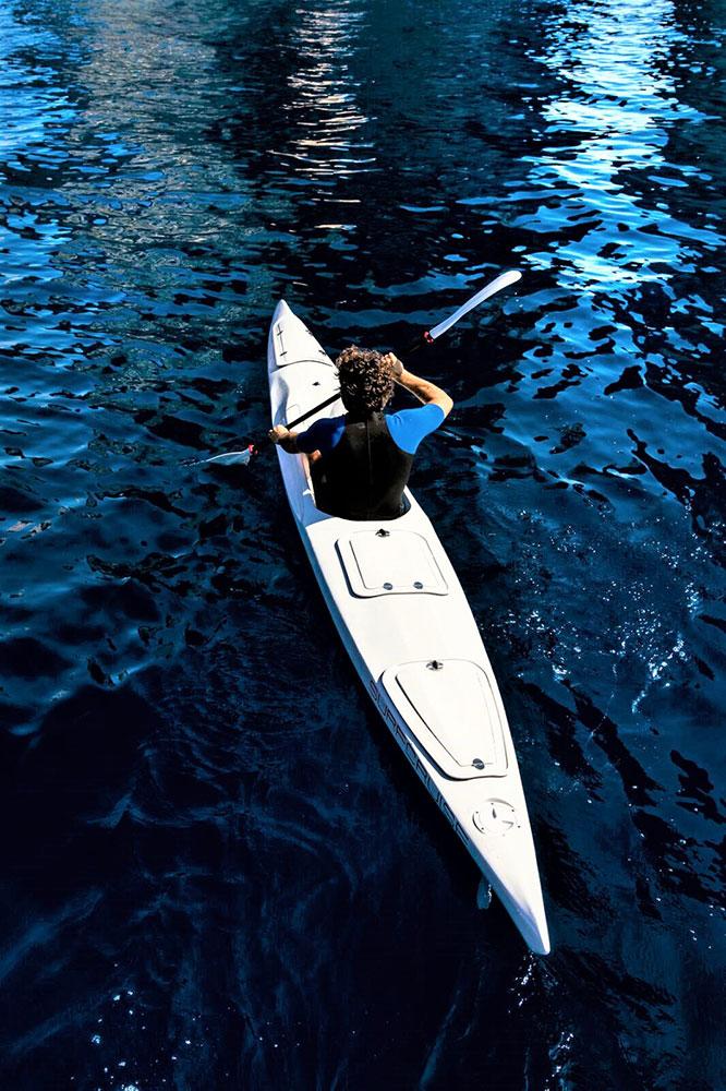 Uomo in canoa nel mare blu kayak Surfcruise
