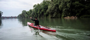 uomo con canoa kayak pagaia ed esplora il fiume
