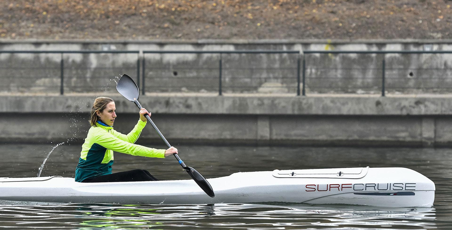 Donna sportiva pagaia sul fiume con canoa kayak surfcruise allenamento