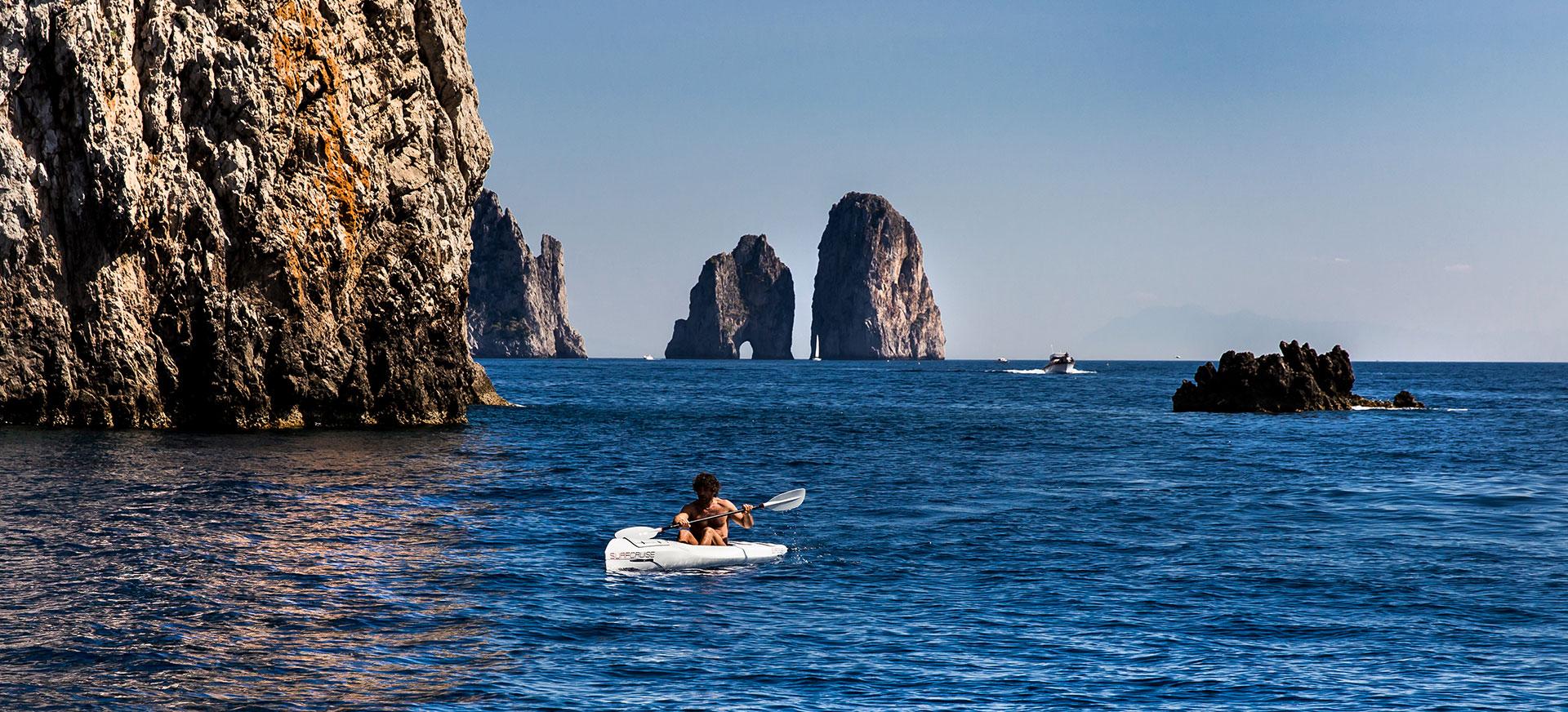 Libertà ed esplorazione del mare in canoa kayak surfcruise a Capri paesaggio Faraglioni