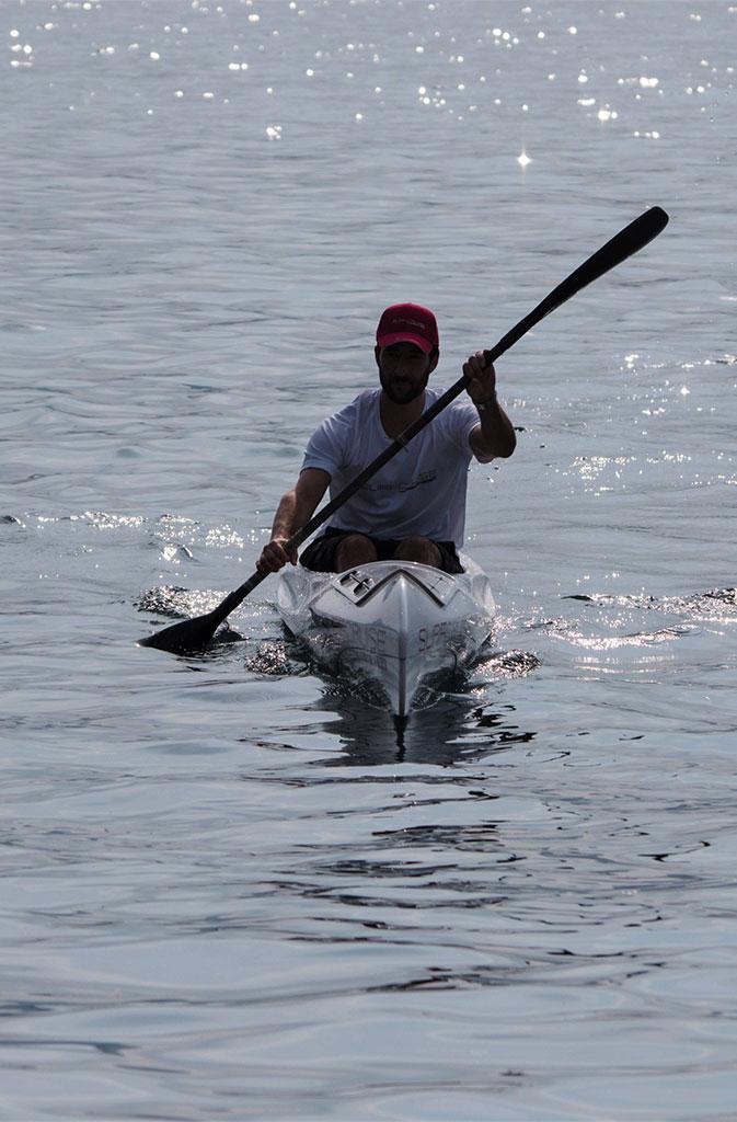 Uomo su canoa in controluce che pagaia su mare, lago, fiume