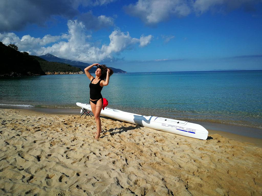bella ragazza al mare su spiaggia con sabbia bianca e canoa kayak surfcruise