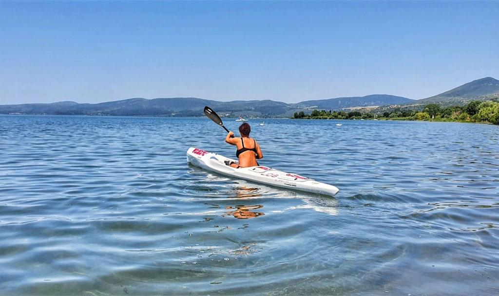 donna sul lago pagaia immersa nella natura incontaminata
