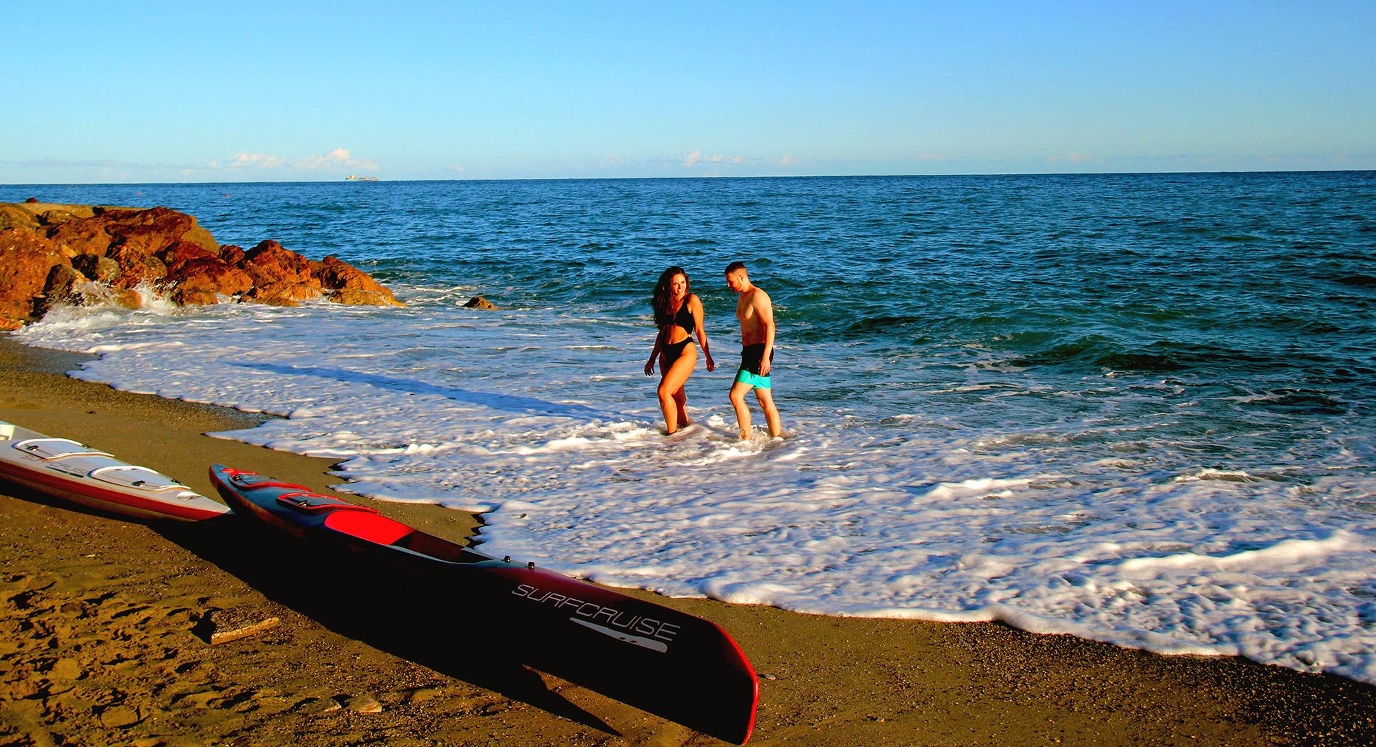 Donna e uomo che cammina sul bagnoacquiga mare azzurro e canoe kayak surfski surfcruise sulla spiaggia